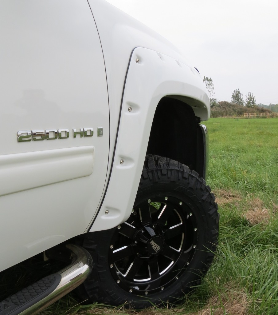 Lifted 2013 Chevy Silverado truck with Bushwacker fender flares, Rough Country lift kit, Nitto Trail Grappler tires, Moto Metals wheels, Road Armor bumper, and Rigid Industries square dually LED fog lights